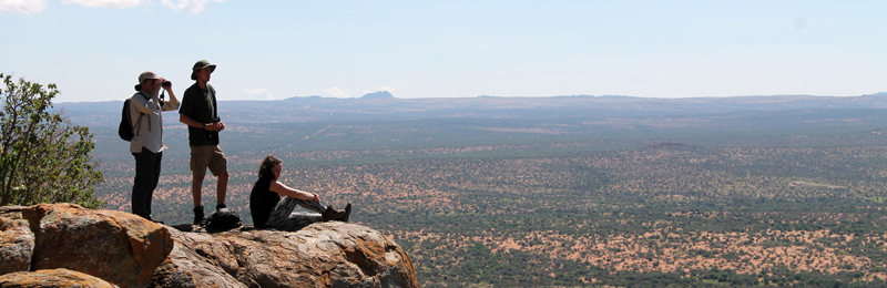 This image shows three students on the african field course. They are standing on top of a large rock looking into the distance. Two of the students are standing while the other is sitting.
