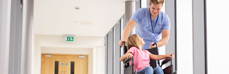 Nurse and child in wheelchair pictured in a hospital corridor